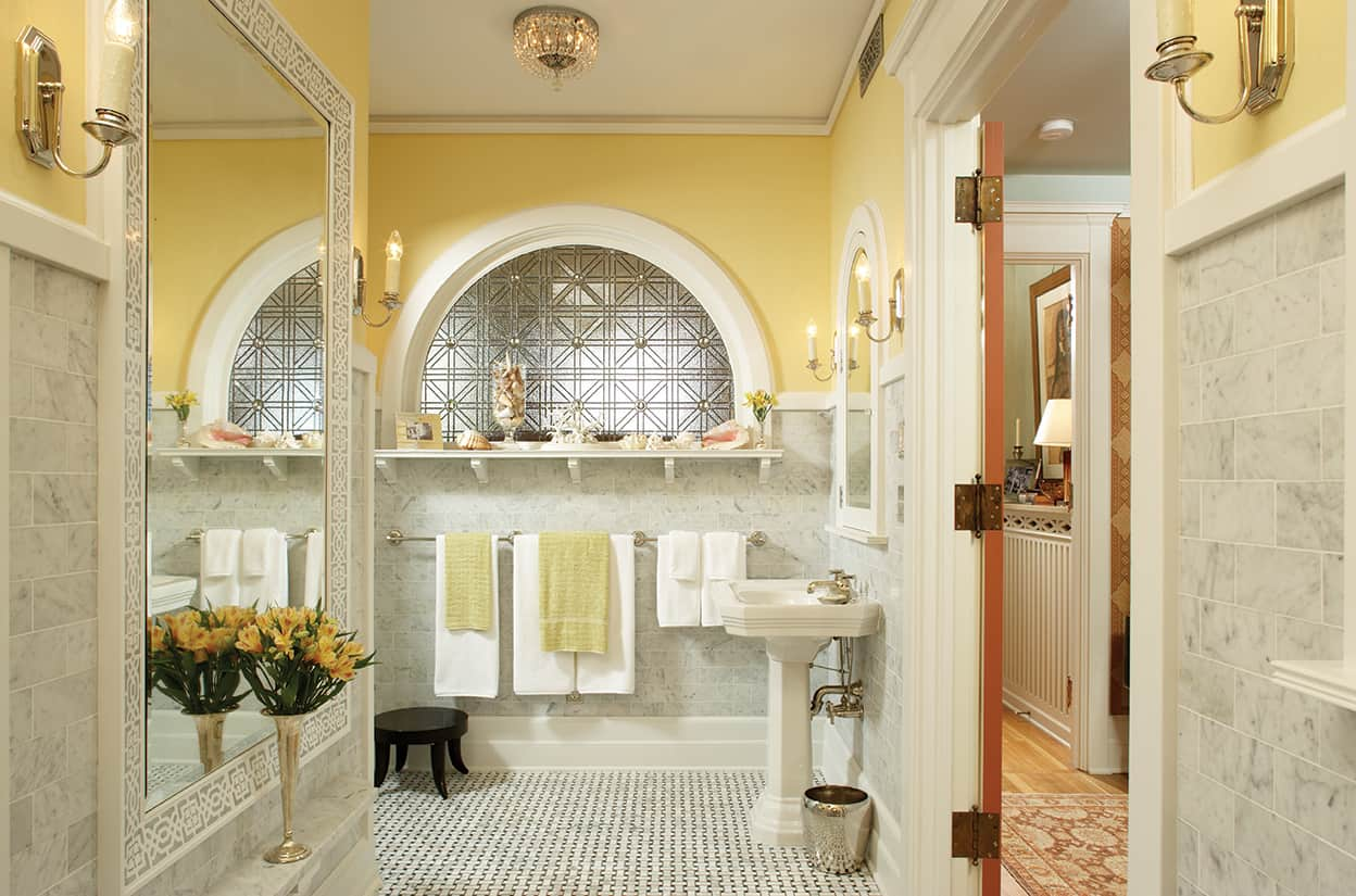 The c-shaped bathroom is spacious and bright, tiled in gray and white marble partway up, and painted yellow above that. It's floored in basket weave tile matching the walls. It features a large, arched art glass window, and an enormous mirror, going down to knee-height.