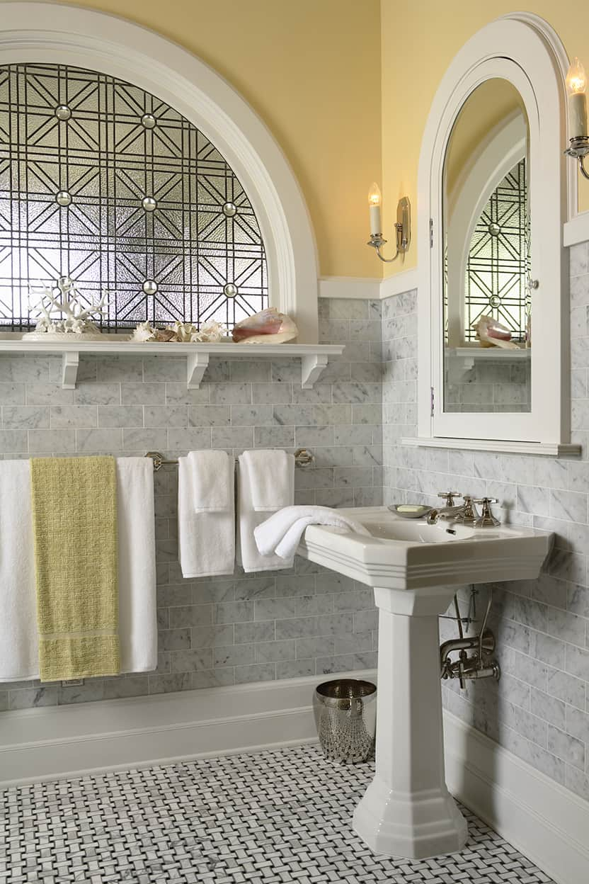 There is a pedestal sink under an arched medicine cabinet, with silver sconces to either side.