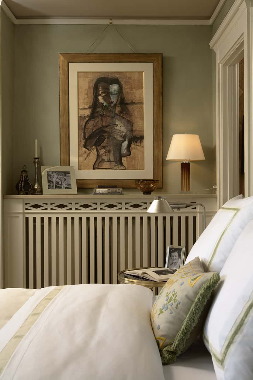 The cozy bedroom is painted a restful, slightly mottled gray-green.