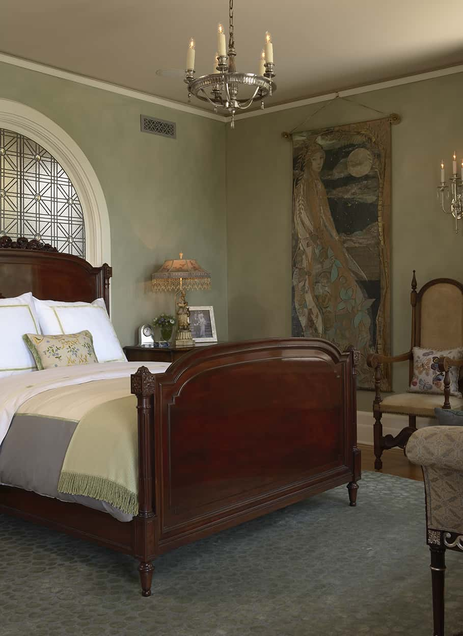 It features another large, arched, art glass window and a large bed made up with sumptuous linens. It has a slightly medieval air with a round, silver, faux candle chandelier, a slightly throne-like chair, and a medieval-influenced art hanging.