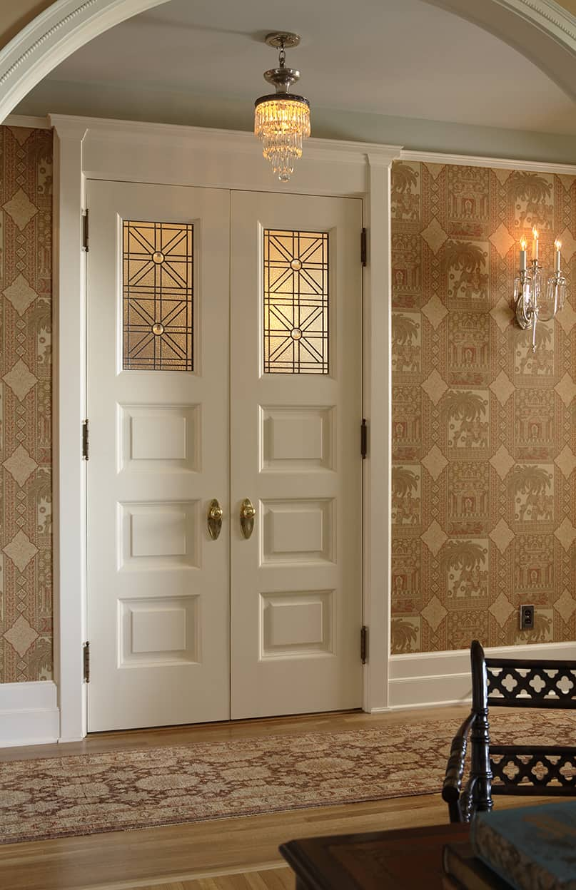 The short hallway is papered in a geometric pictorial print in tans, and is illuminated by a crystal chandelier and sconce, matching many of the others in the suite. Double doors with art glass panes of squares made up of triangles (the pattern used throughout the suite) lead to the bathroom. The doors are white on the hallway side and brown on the bathroom side.