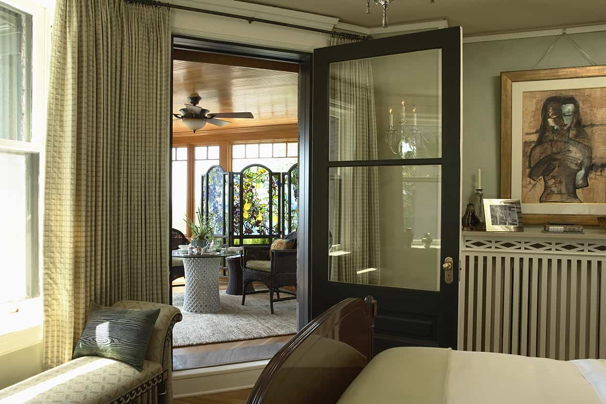 A wide door from the bedroom leads onto a porch, walled in windows set in natural wood to match the ceiling. It's furnished in comfortable wicker, and decorated with a gorgeous colored glass screen.