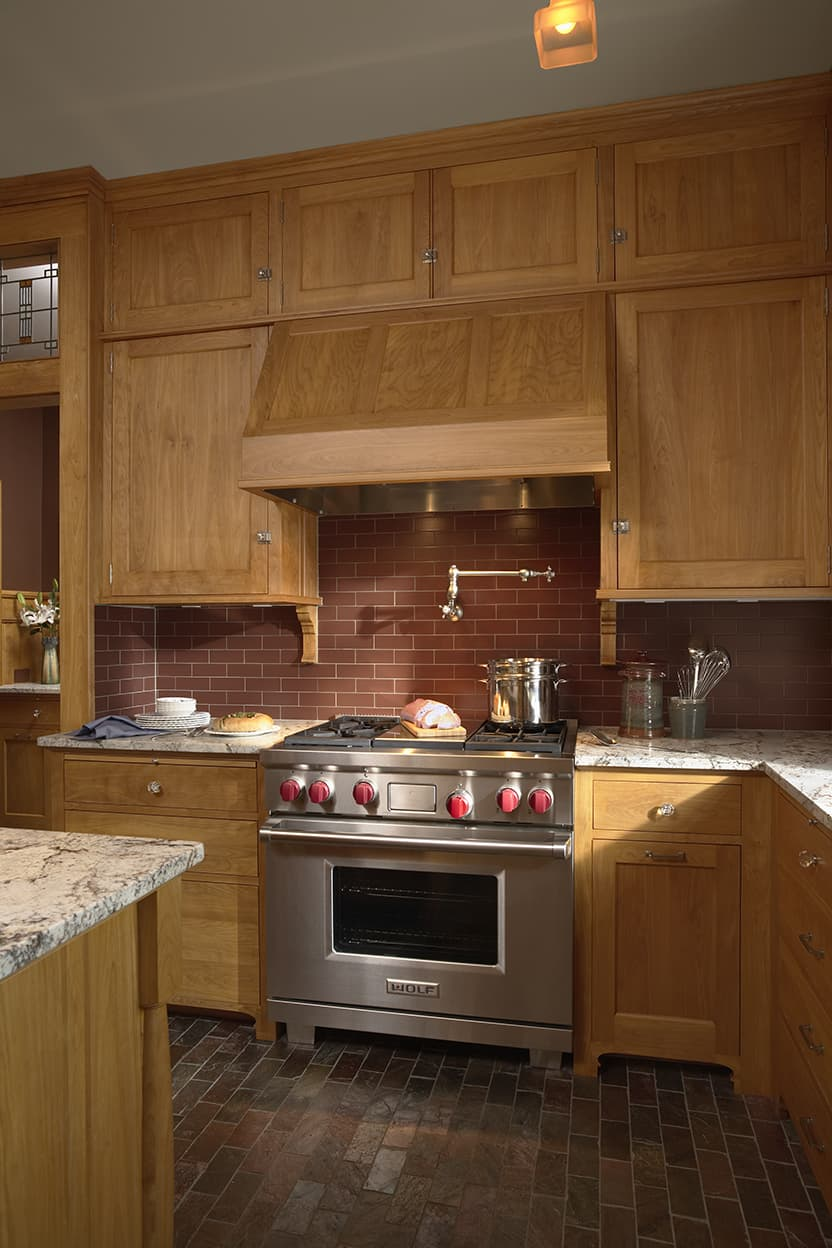 The red birch kitchen cabinetry is simple yet elegant, with brushed silver pulls and glass knobs. The serious stainless steel stove sits under a pot filler faucet.