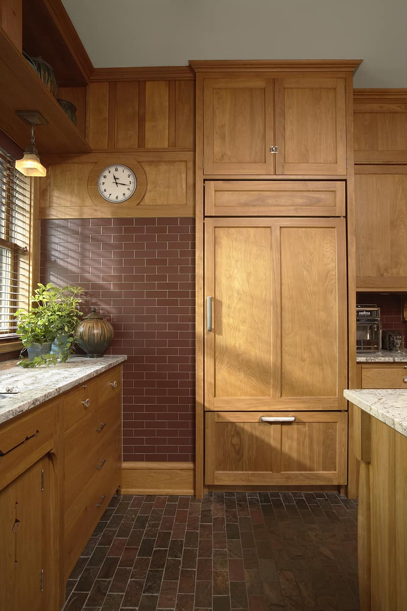 Most of the appliances are hidden behind cabinetry. The custom backsplash tile is a warm red brown, and the slate floor runs to brown and pink tones, both in matching subway tile size.