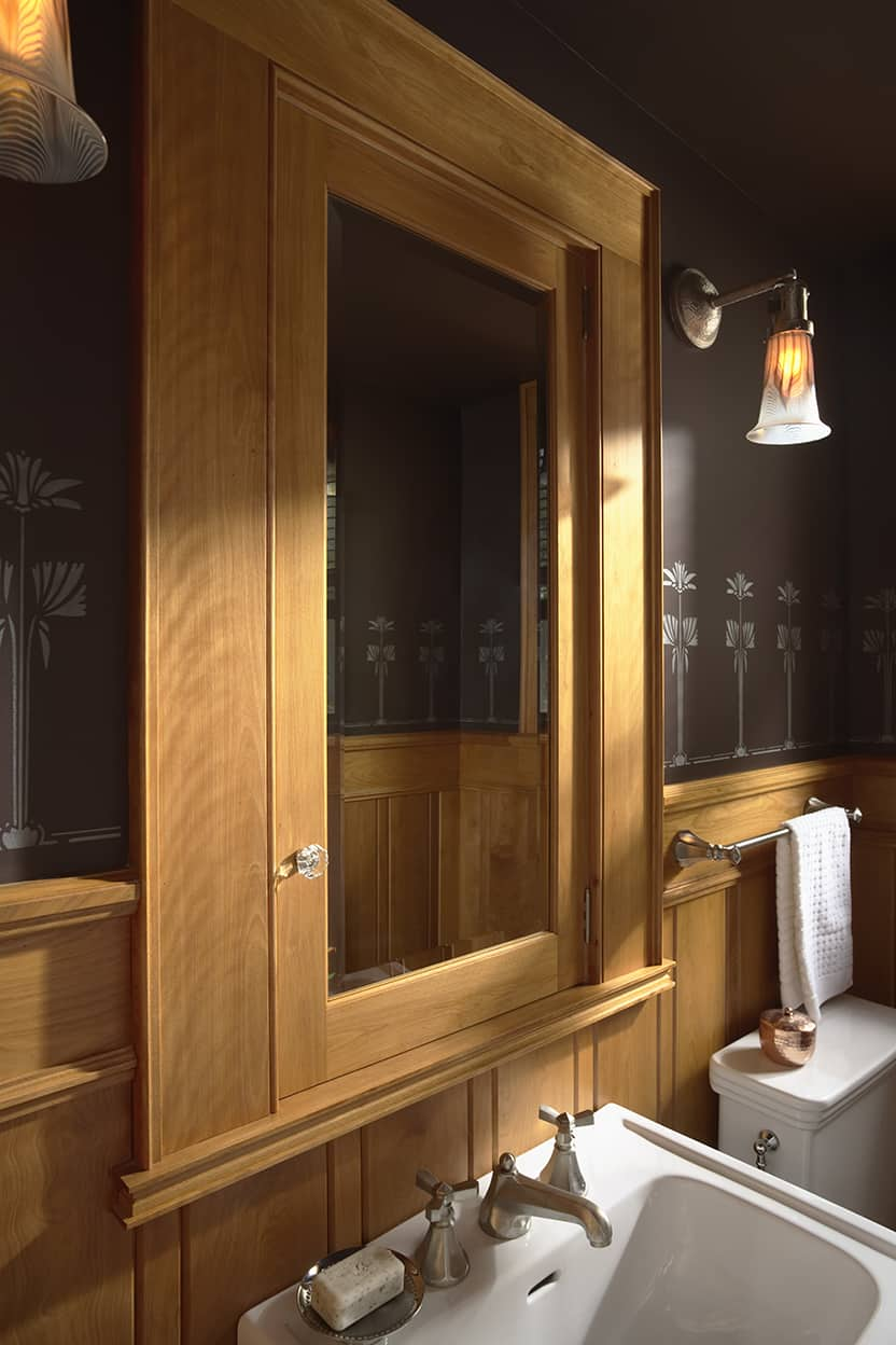 The powder room has natural wood panelling and dark brown walls with a silver stylized floral stenciled design. The sconces are brushed silver with art glass shades.
