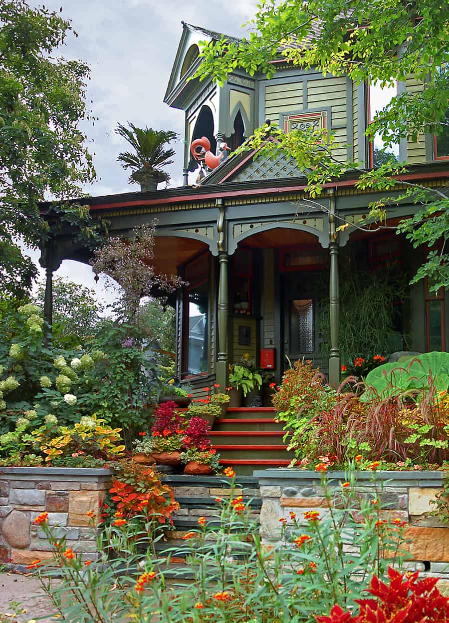This newly painted lady, with its whimsical, ebullient, and intricate trim, is resplendent in 4 colors, in a theme similar to the old but, like the trim, enhanced. The main color is a light sage green, with the trim in a darker sage and a darker orange-red. The bright orange-red porch floor and step treads add that final pop of color that makes the whole combination sing.