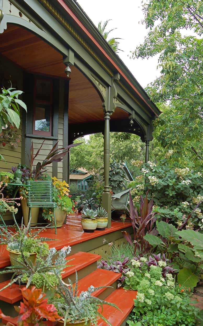 The new porch has columns that gently swell and narrow, leading up to fancy trim that harmonizes with the surrounding foliage. The lines between garden and house are further blurred by a plethora of potted plants on the porch.
