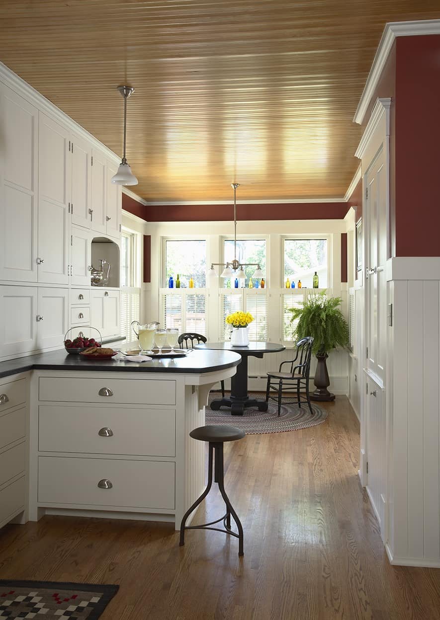 Kitchen small peninsula and red breakfast area with plentiful windows