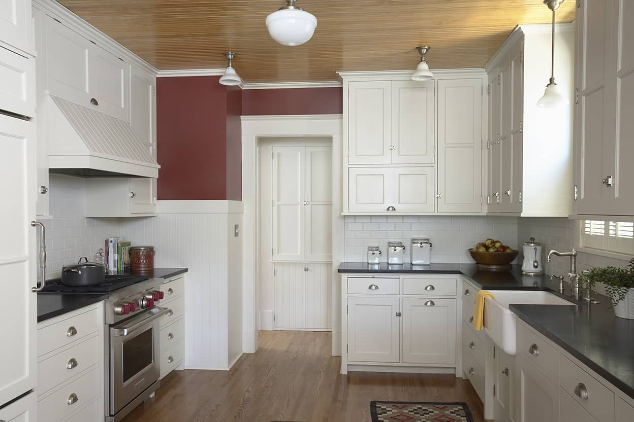 Kitchen showing stainless steel stove, hardwood floors, and extra storage