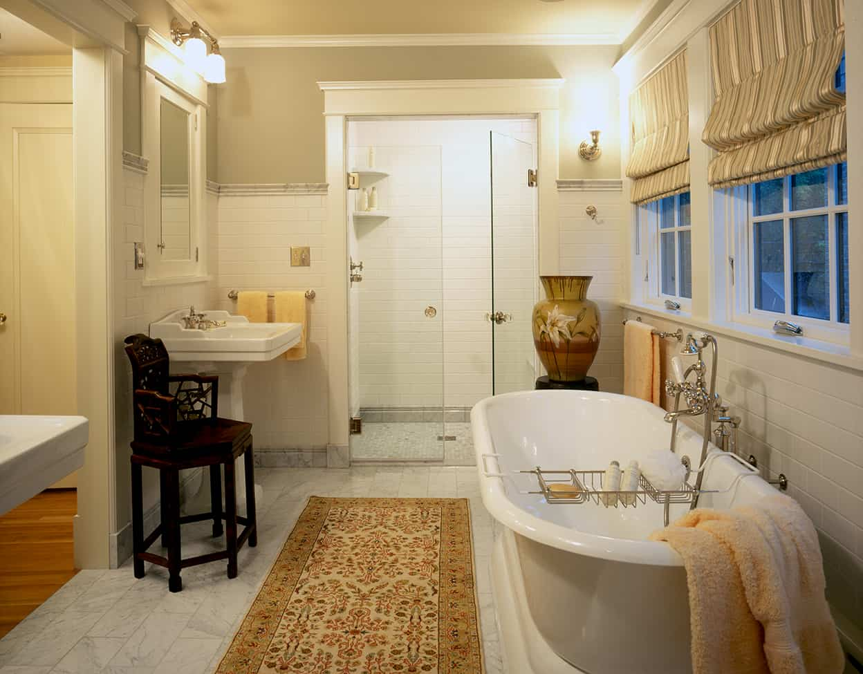 This bathroom is neutral, restful, and very period, but also very functional, with a roll-top bathtub, a generous shower, and two pedestal sinks with medicine cabinets.