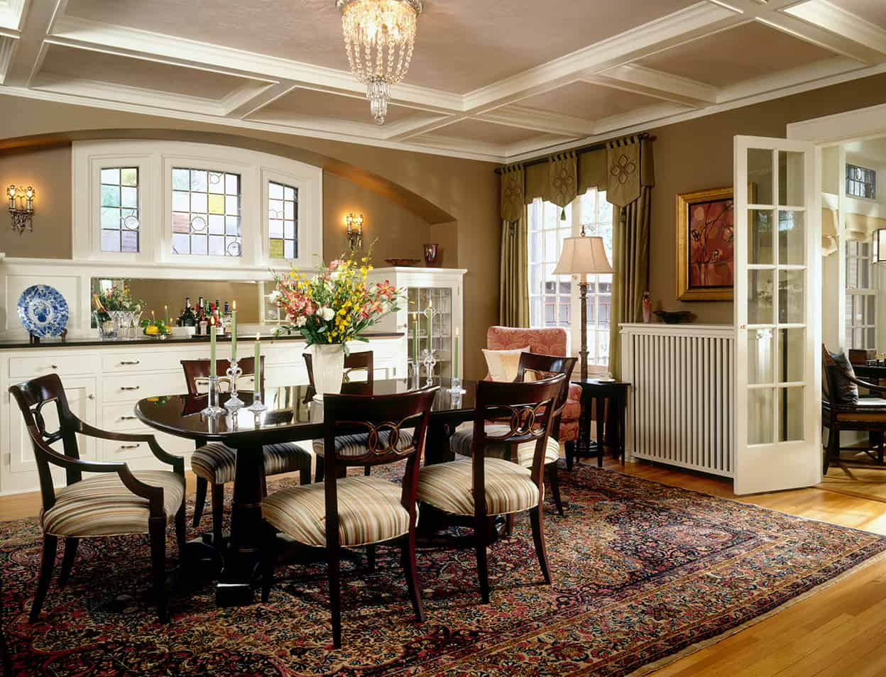 With it's coffered ceiling, elaborate built-in buffet with art glass, crystal sconces, and mirror all set into an arched niche, and elegant furniture, this dining room would enhance any meal.