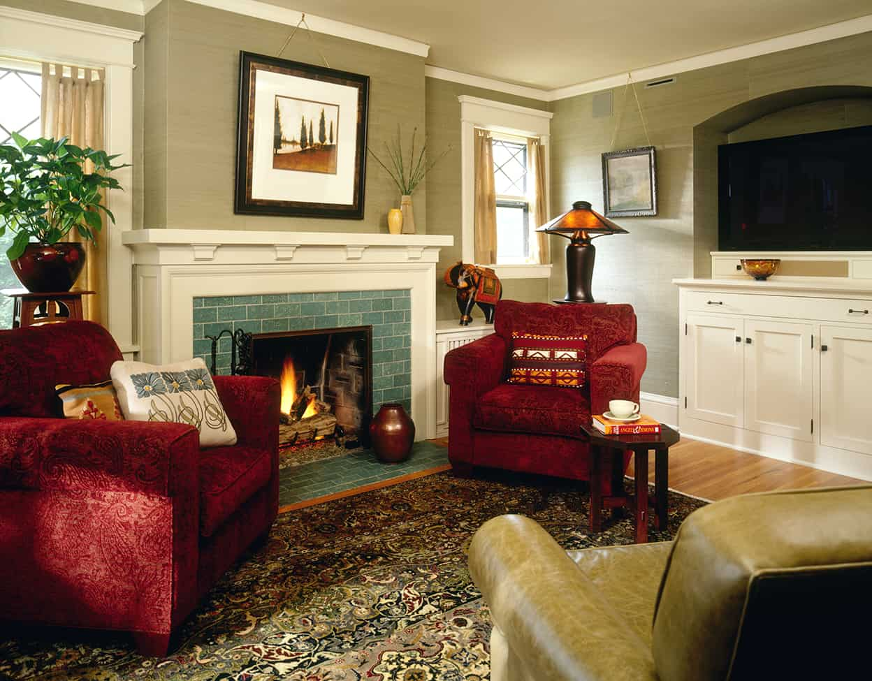 While the family room is a bit simpler than the formal living room, it's no less comfortable with its overstuffed furniture, fireplace, and warm color palate. The fabric-textured wallpaper, Persian carpet, and beautiful objet d'art also give it a quiet elegance.