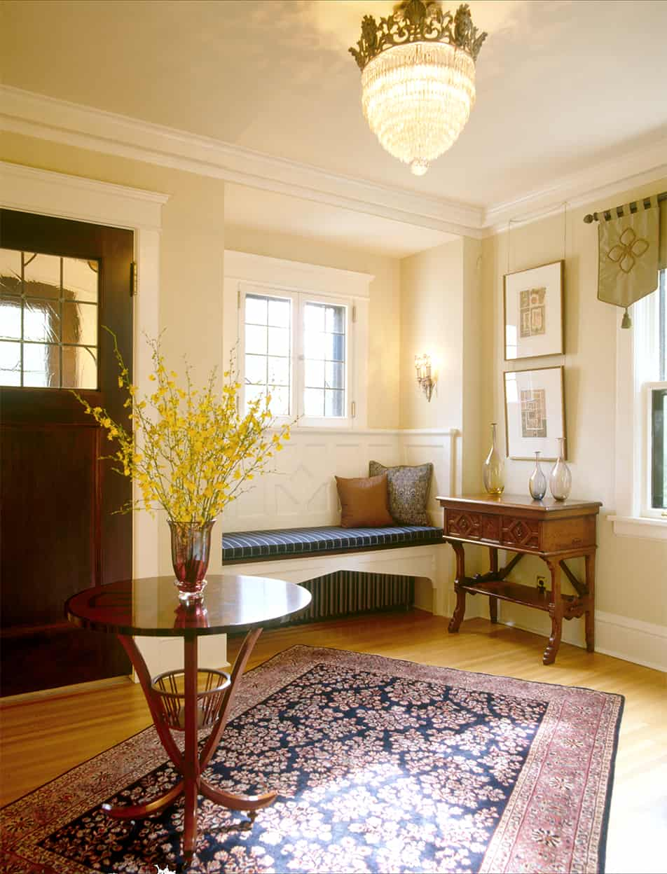 Less a foyer than an entrance hall, this neutral space's built-in bench, rug, crystal chandelier, and beautiful furniture has the same luxurious feeling as the other public spaces.