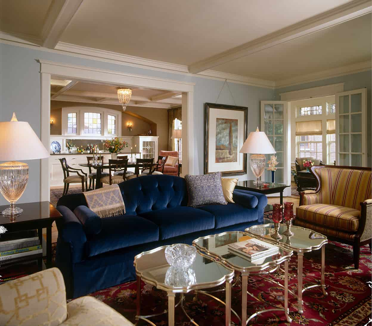 While much of the rest of the living room is neutral, the light blue walls, royal blue velvety couch, and red Persian rug add pops of color to the luxurious interior.