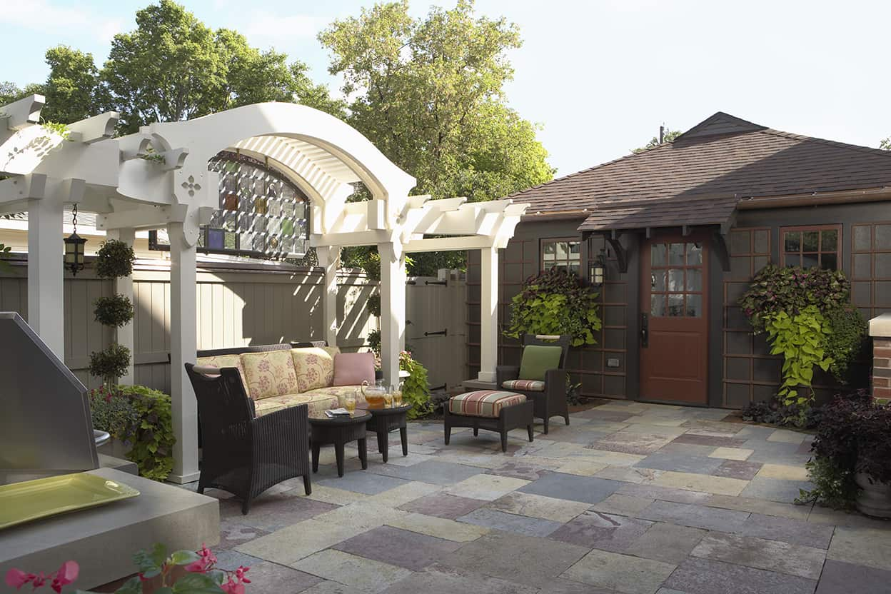 The backyard has been turned into a comfortable outdoor living area for cooking, dining, and relaxing, accented with a slate patio floor and a sculptural pergola with a stained glass shade.