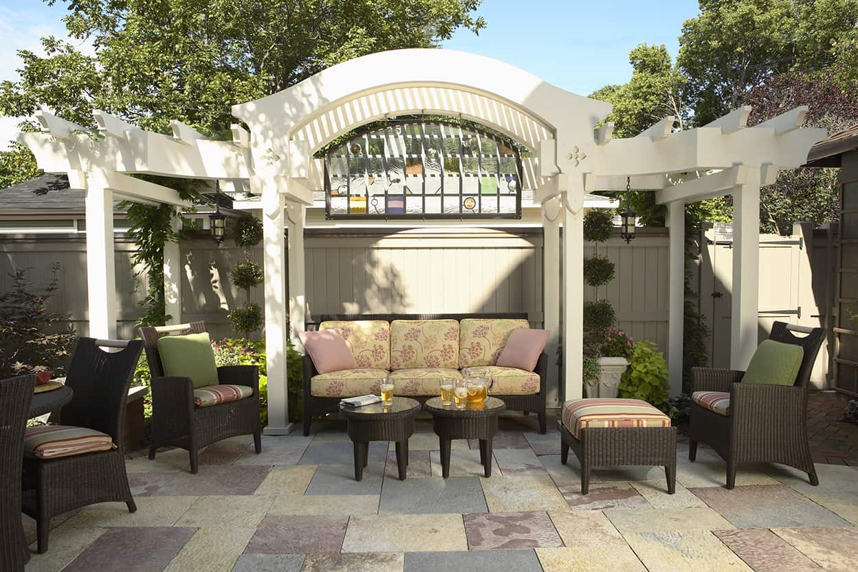 In the backyard comfortable faux wicker cushioned furniture makes for a comfortable seating area.