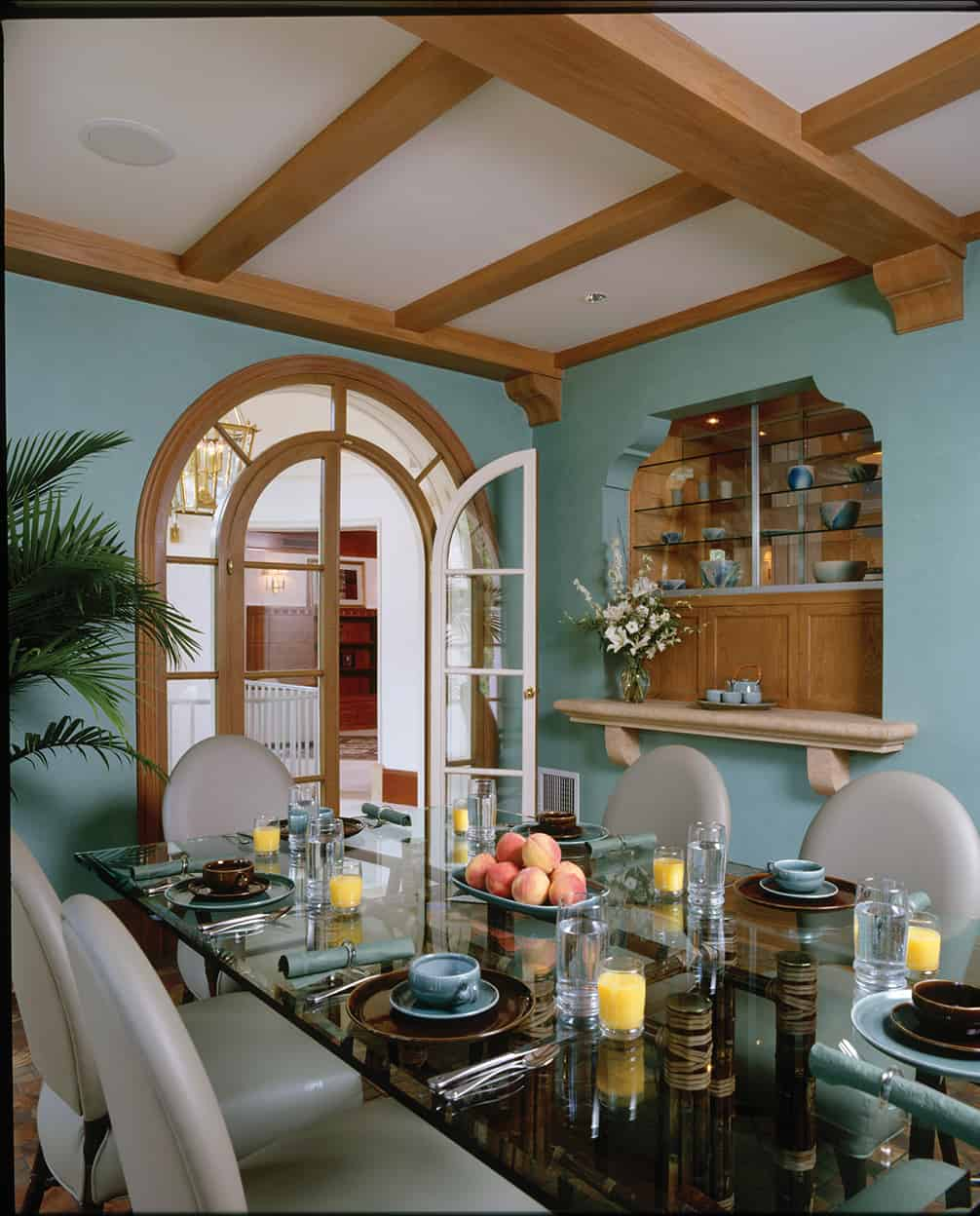 The breakfast room features seafoam walls, an arched French door, a cross-beamed ceiling, a smoked glass-topped table, and white leather chairs. The unusual built-in china cabinet starts at waist height and its closed cabinetry and open glass shelves fit into a nook carved in the wall above a stone shelf.