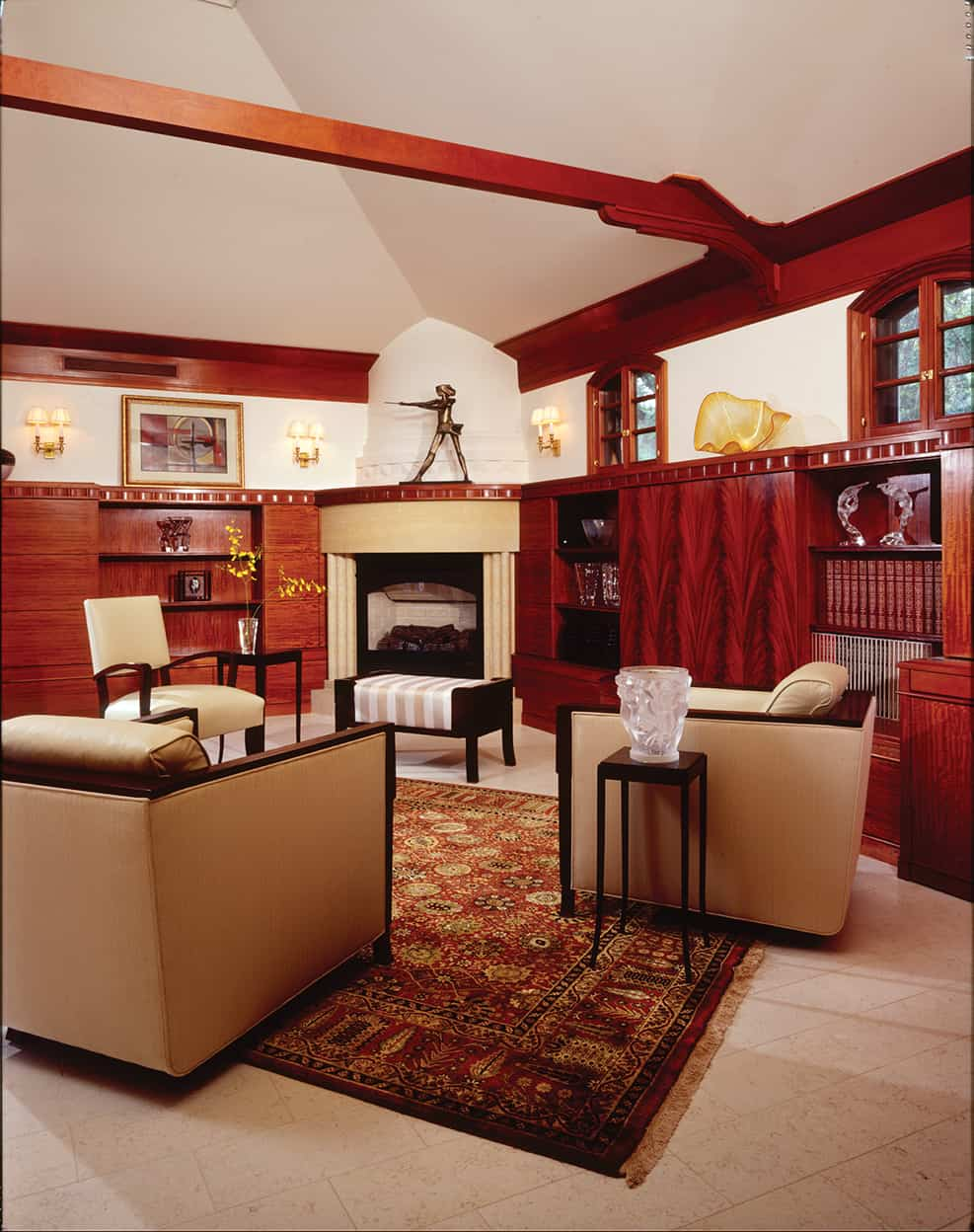 The family room has white walls and a vaulted ceiling with elegantly carved beams. The rounded corner fireplace is of cream stone, and the white stone floor (which continues into the kitchen) is softened by an oriental rug in browns, reds, and golds.