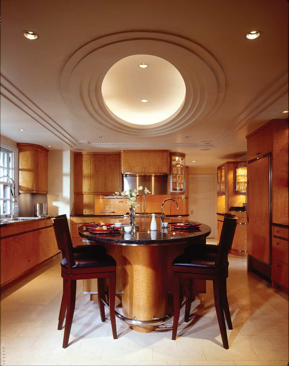The kitchen's other dominating feature is the ceiling, trayed in rectangles near the perimeter, with ovals near the center, surrounding a glowing central oval, lit by can lights. The cabinetry is light toned woods with a number of glass display cabinets.