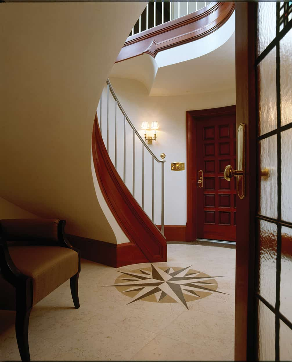 The new entrance tower's sweeping staircase rises above a stone floor with a compass rose medallion. The entranceway has white walls and reddish-brown toned woodwork. The staircase's brushed silver railing contrasts with the brass hardware used elsewhere.