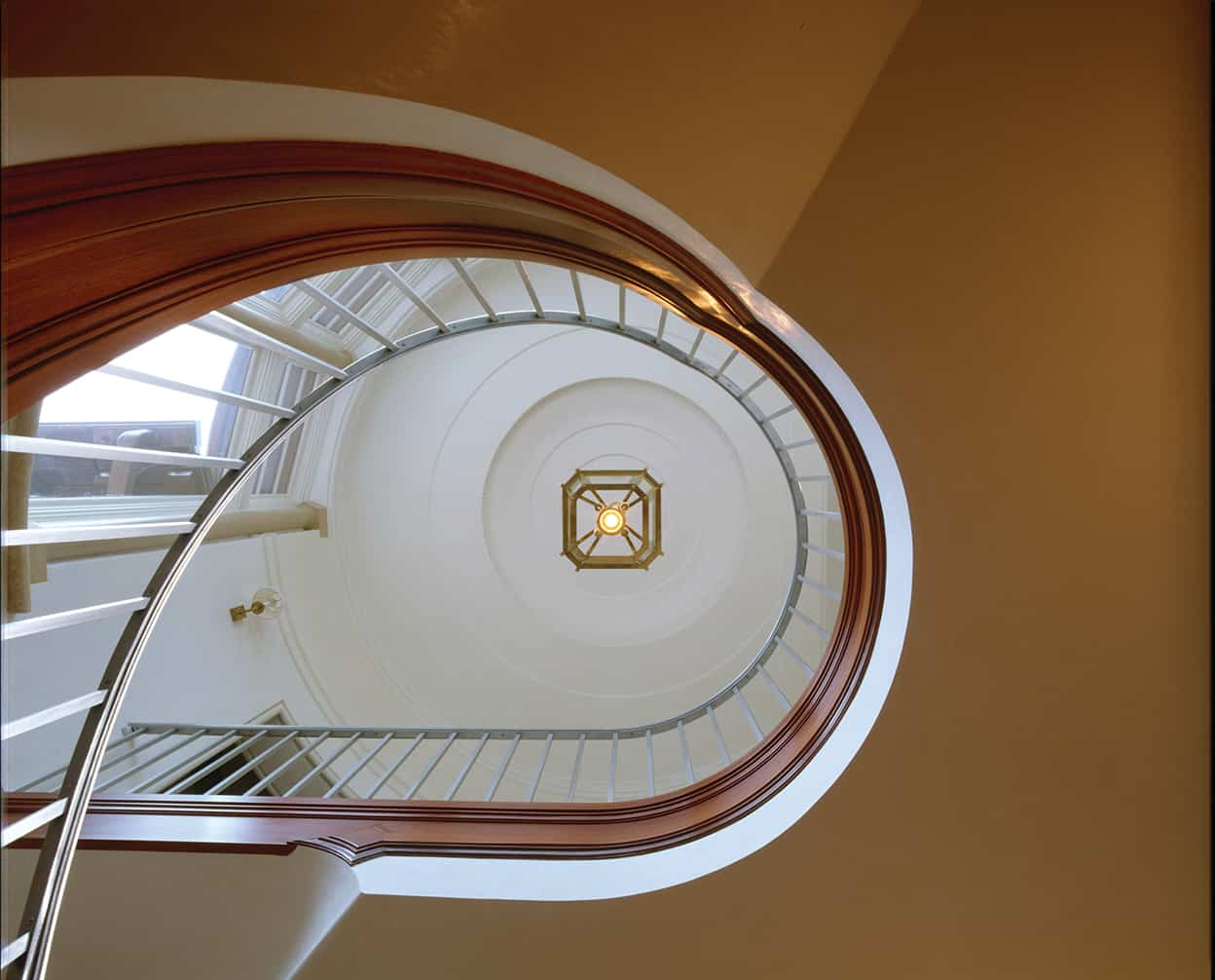 Looking up through the sweeping staircase's circle, we see the tower's circular trayed ceiling and wall of windows.