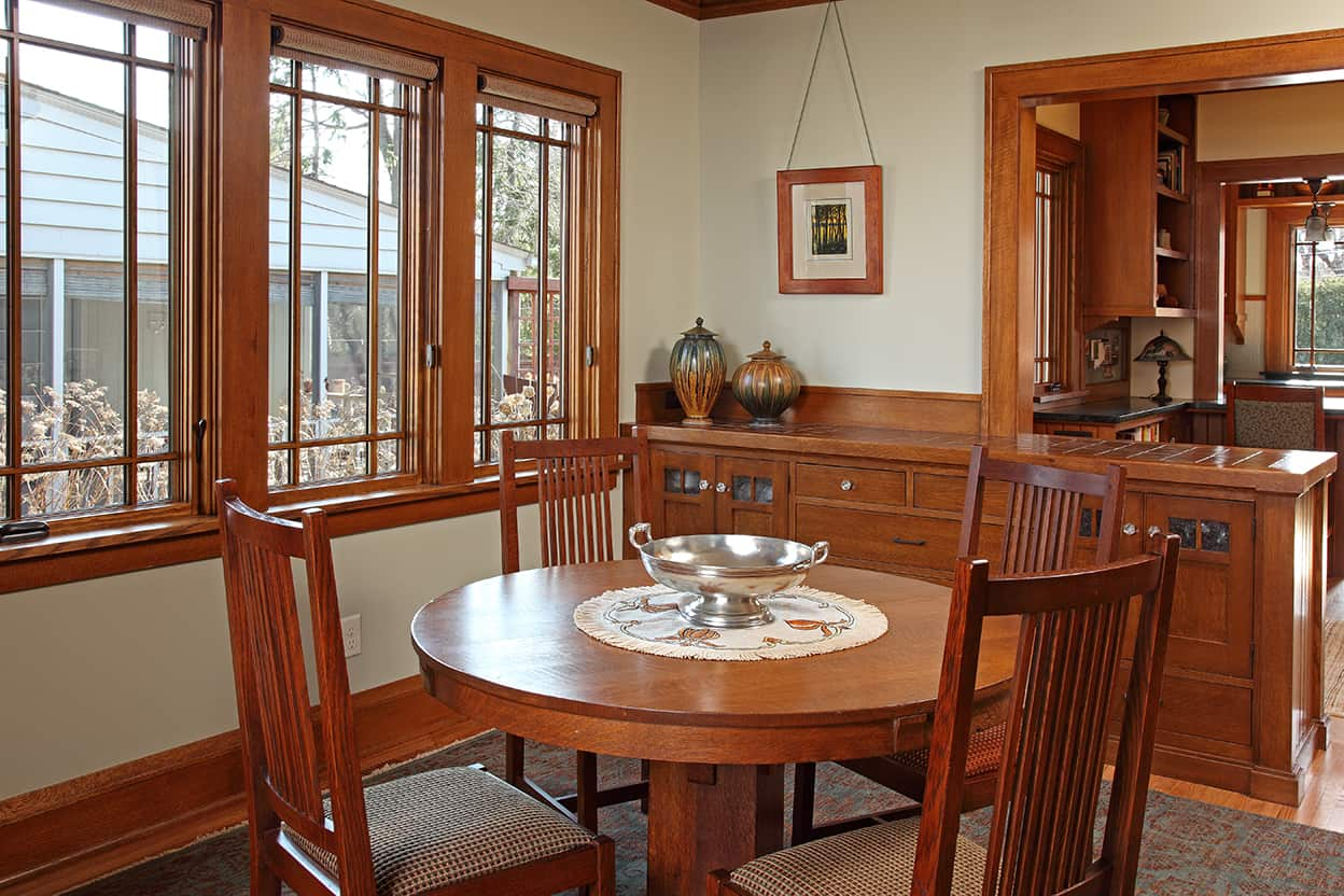 The dining room has a round pedestal table with squared stick-back chairs and a built-in buffet, which mirrors the peninsular kitchen eating area. Together they define the back entry. Large windows, green-gray walls, and a muted greenish & brown paisley rug complete the space.