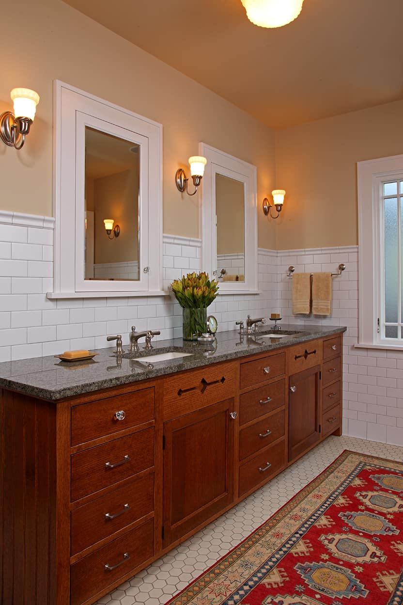 The Master Bath has white subway tile and woodwork and sand colored walls. A brownish, dappled stone tops the generous double vanity, and the bottom-mounted sinks have old-fashioned chrome fixtures. A red oriental rug covers much of the white hex-tiled floor.