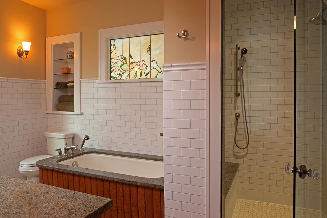 The Master Bath also has a large glass-walled shower and a tub boxed in with natural-toned bead board and stone to match the vanity. There's a floral stained-glass window in peaches, pinks, and greens over the tub.
