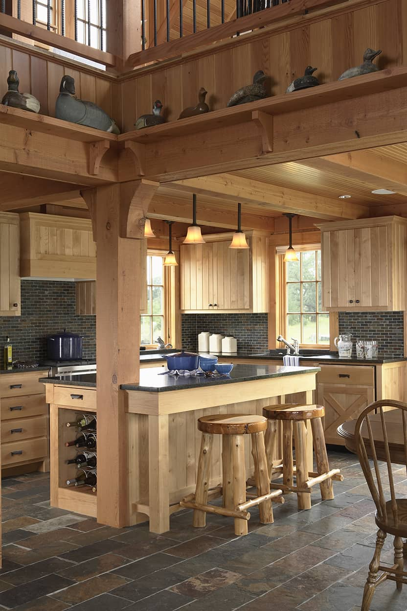 The kitchen uses the same simple cabinetry and millwork used throughout, as well as a slate backsplash and dark stone counters. The generous island has bar stools made of sticks.