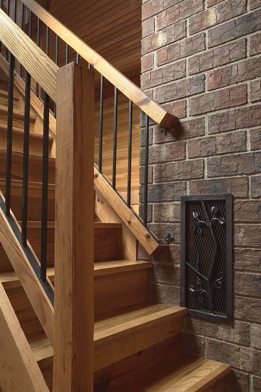 The simplicity of the materials are off-set by some meticulous decorative details, such as the iron tree wall-art at the bottom of the stairs.