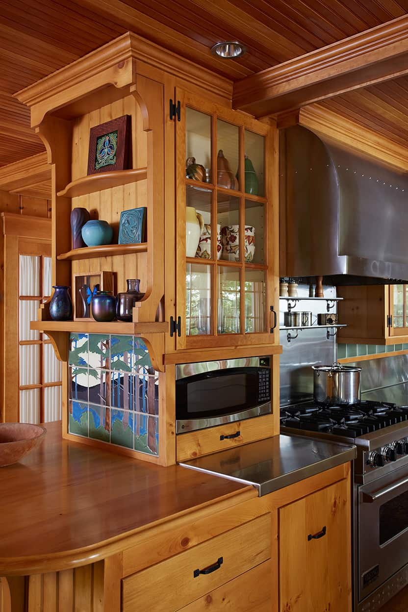 Main level kitchen small peninsula with art tiles and open shelves and glass cabinet with objet d'art