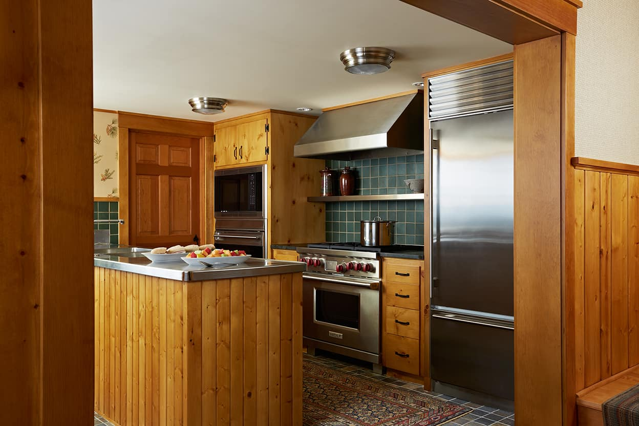 Catering kitchen with slate laid out in small squares on the floor and stainless steel appliances