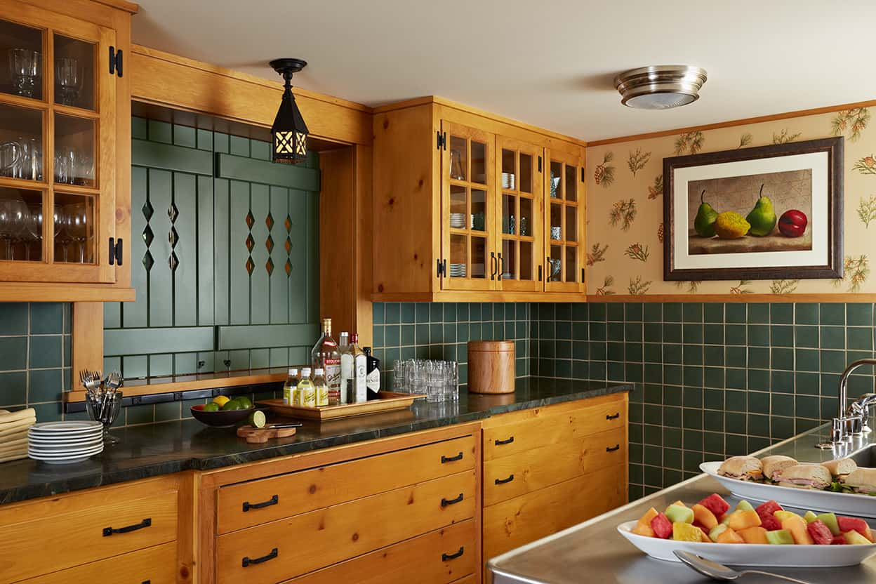Catering kitchen with pine cabinetry with glass doors, dark green-gray square tile backsplash, and floral wallpaper