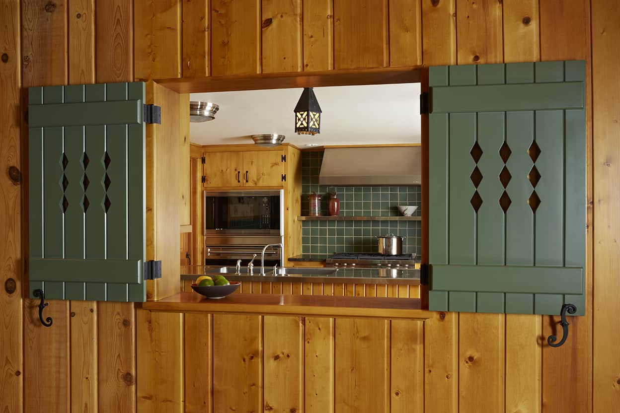 Catering kitchen pass-through looking into the kitchen with open dark geen-gray shutters