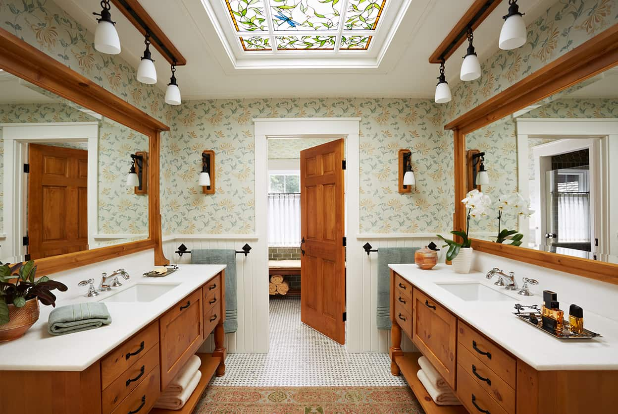 Master bath's massive mirrors and natural wood vanities, one of each on either side of the room, along with the floral wallpaper and white woodwork and counters