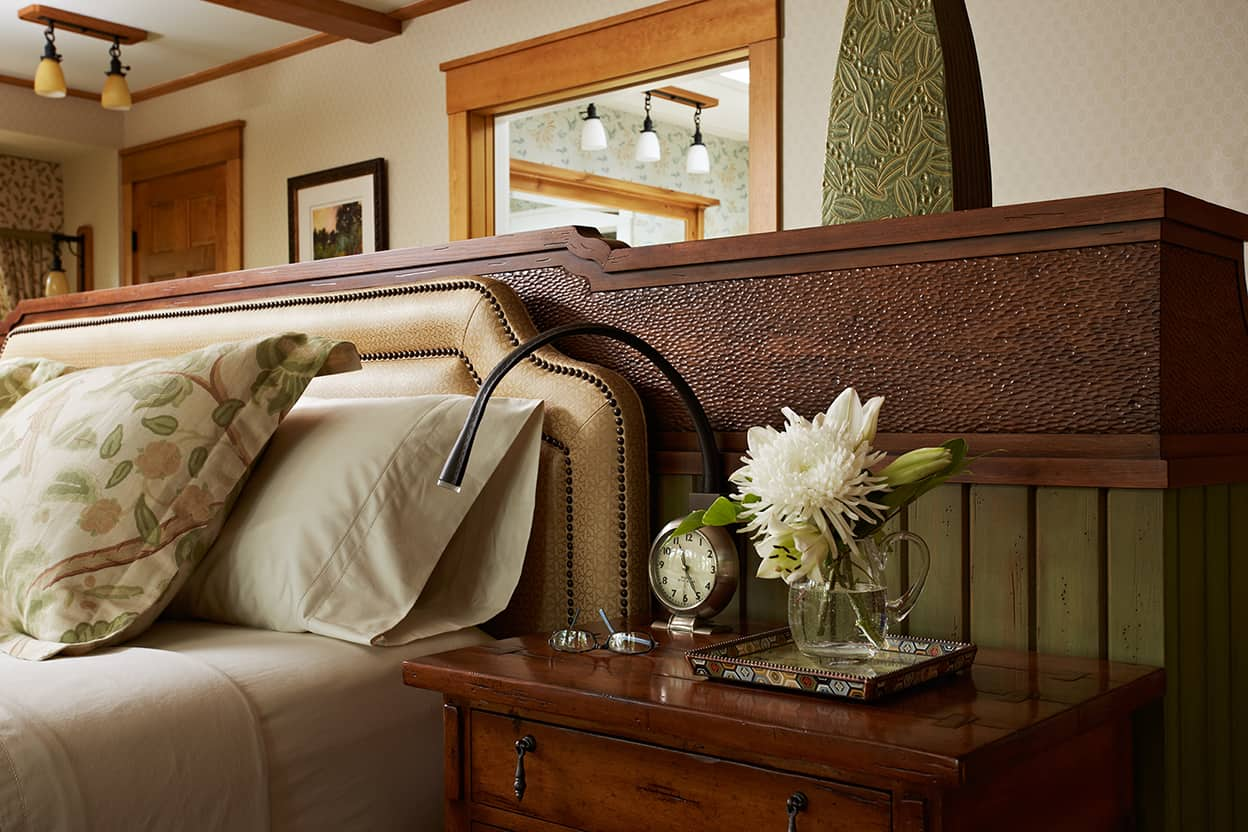Master bedroom tan padded headboard, wood bedside table with dark, distressed finish, and back of dresser
