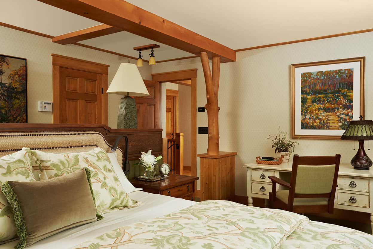 Master bedroom luxurious bed, antiqued desk and subtle off-white wallpaper