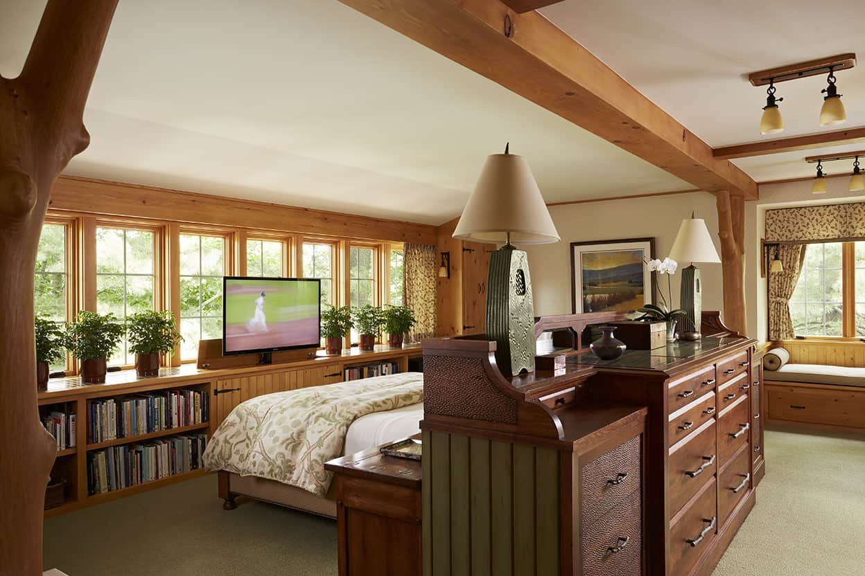 Master bedroom with natural wood woodwork, pendant lighting, muted blue-green carpet, low bookshelves under the windows, and a television that lowers into cabinetry when not wanted