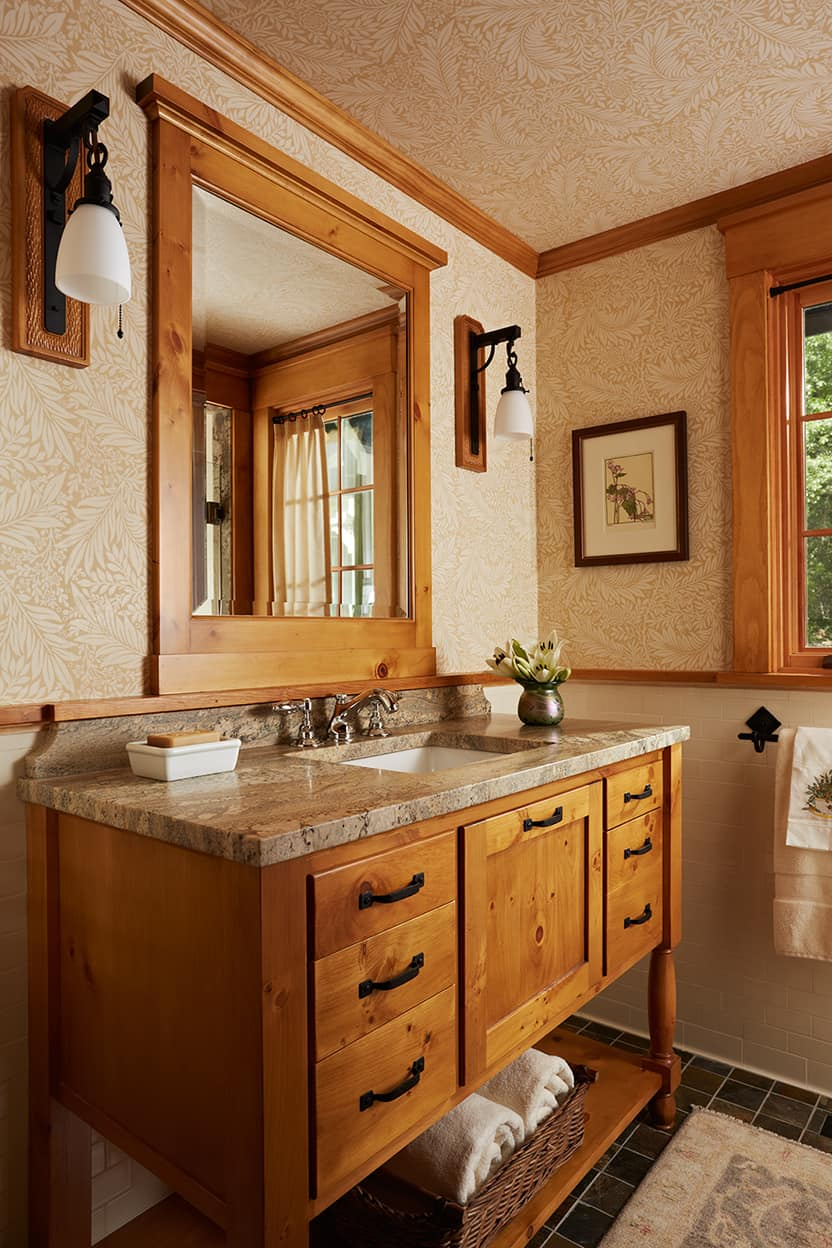 Powder room natural wood vanity and woodwork with brown stone counter, tan leaf patterend wallpaper and pendant dark metal pendant sconces