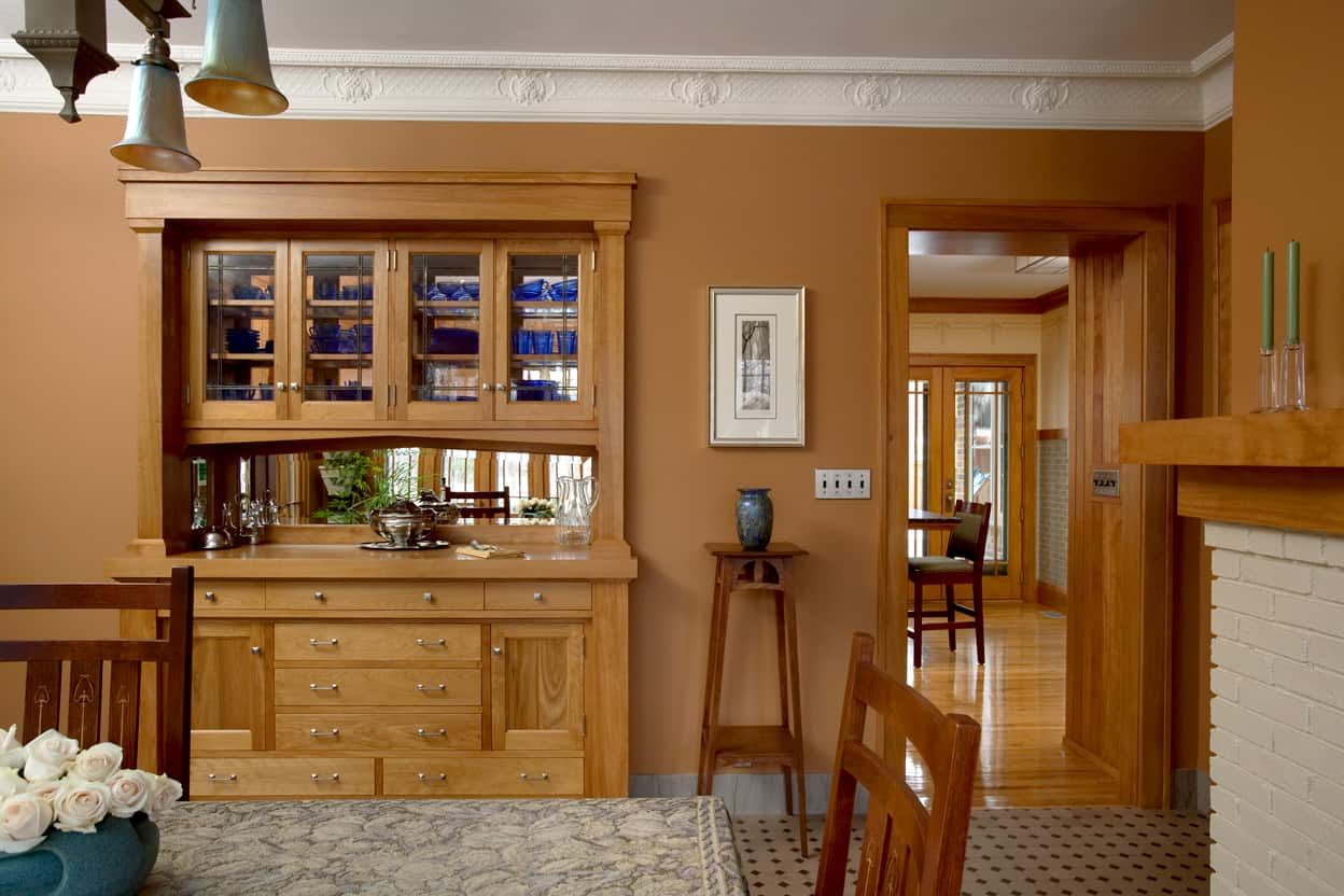 Dining room natural wood buffet with glass upper cabinets showing through to the kitchen