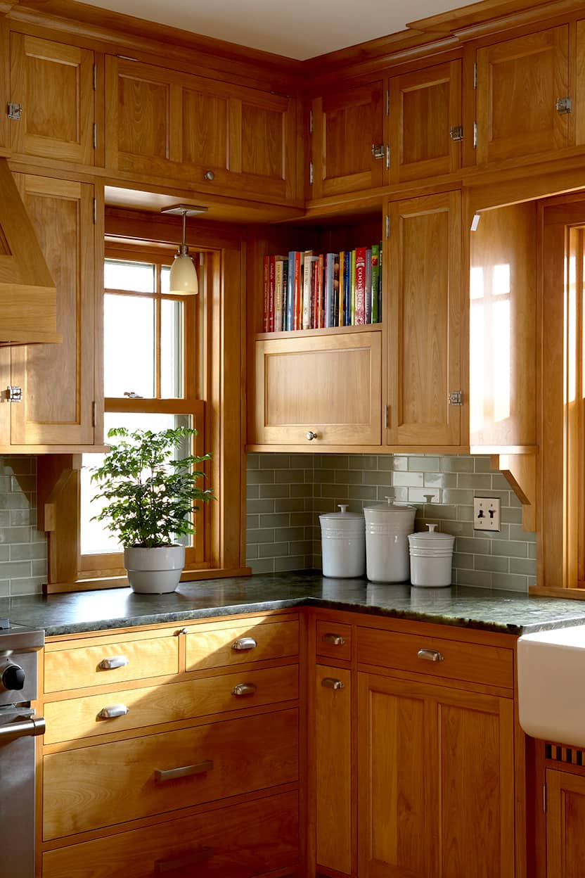 Kitchen natural wood cabnetry, gray-green tile backsplash, and gray-green mottled stone counters