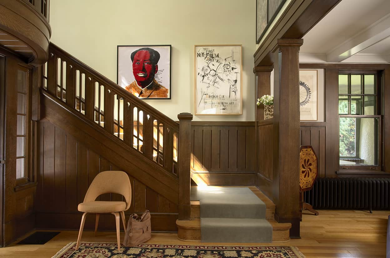 The houses light wood floors contrast with the darker wood paneling and woodwork in this entrance hall. The cut out stair rail and the curved landing over the front door add elegance to the space.