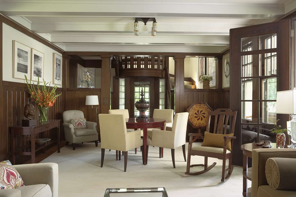 The living room has a seating area, as well as a table and chairs. Its beamed ceiling, painted a glossy bright white, reflects light from the wall of windows with a glass-paned door.