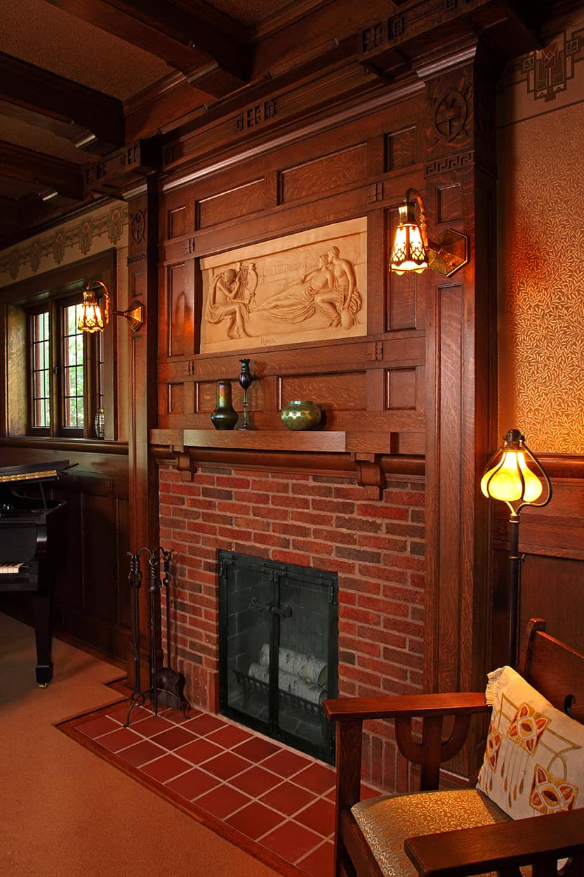 Restored fireplace from the side highlighting the depth of the relief and the way the fireplace highlights the high Arts & Crafts decor of the room..