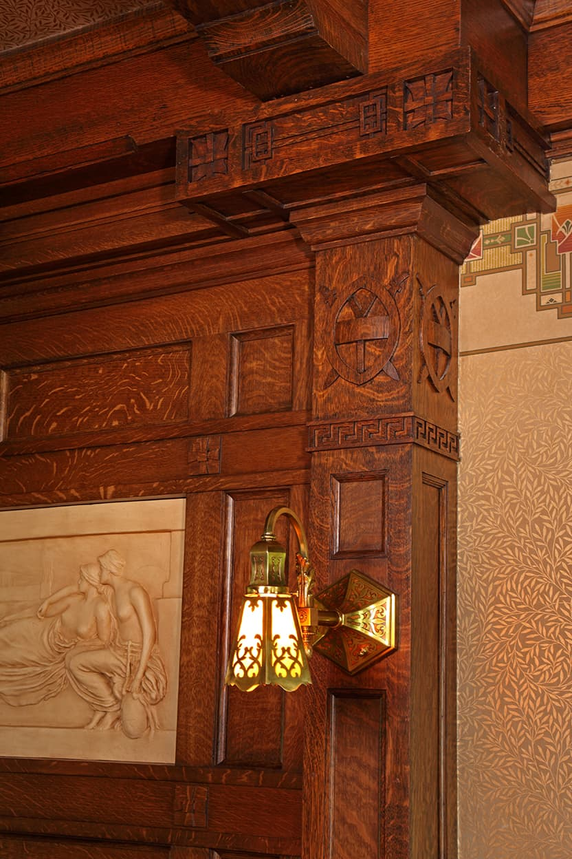 Restored intricately carved but restrained woodwork details on the chimney breast, crown molding, and ceiling beams. Includes a gracefully ornamented glass and brass sconce.