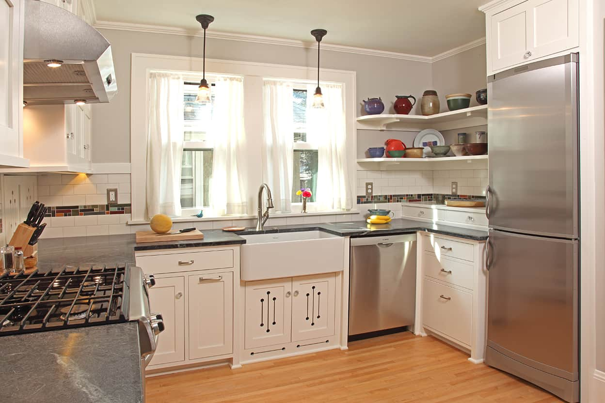 Overview of kitchen featuring simple yet beautiful cream cabinetry, gray stone countertops, warm light gray walls, honey-colored wood floor, and a white farmhouse sink under two windows and two glass pendant light fixtures.