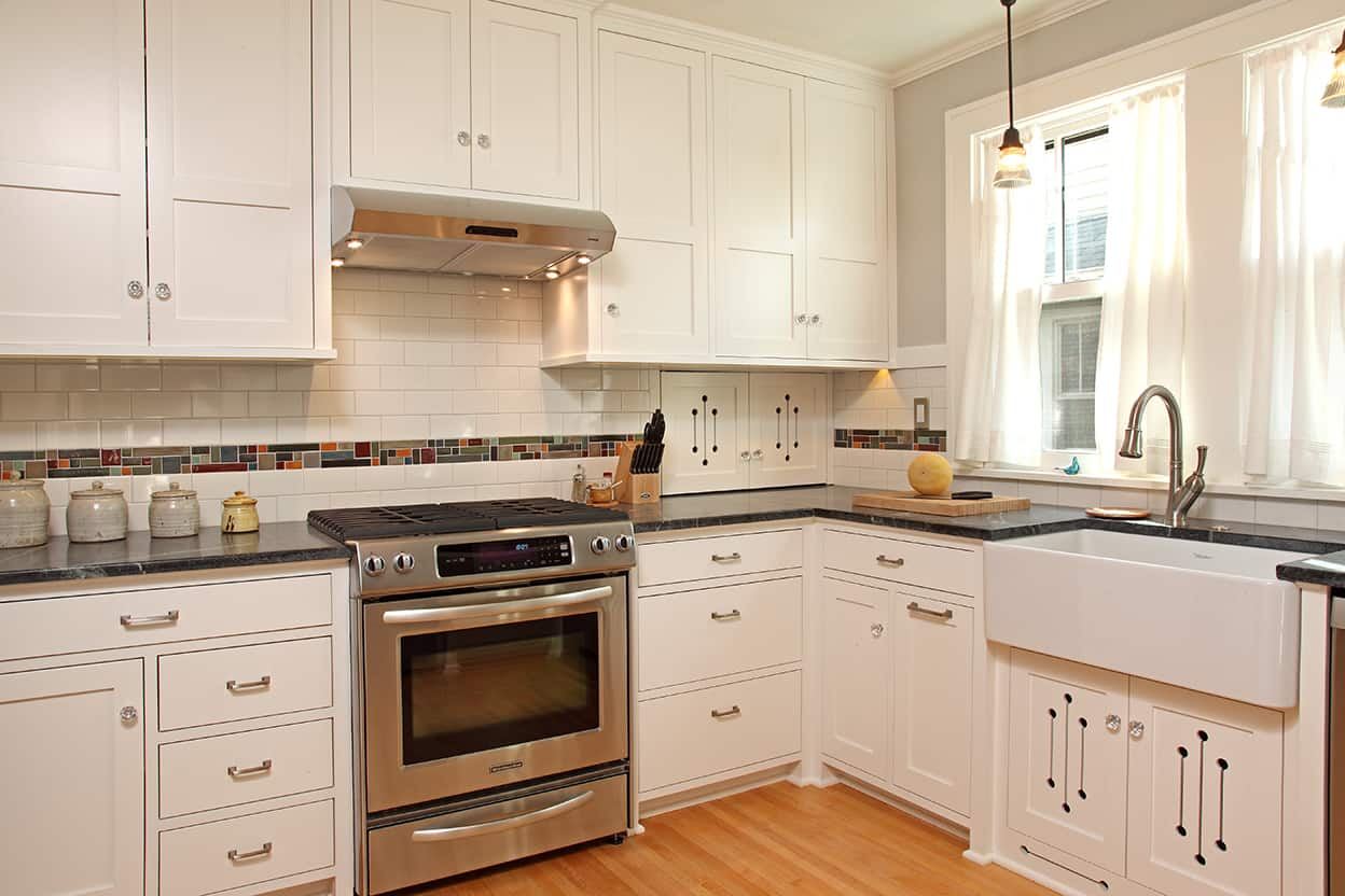 Features the stove and the cream subway tile backsplash with a band of earth-toned multi-colored tiles. The cabinet pulls are silver toned while the knobs are glass. Most of the lower cabinetry is generous drawers.