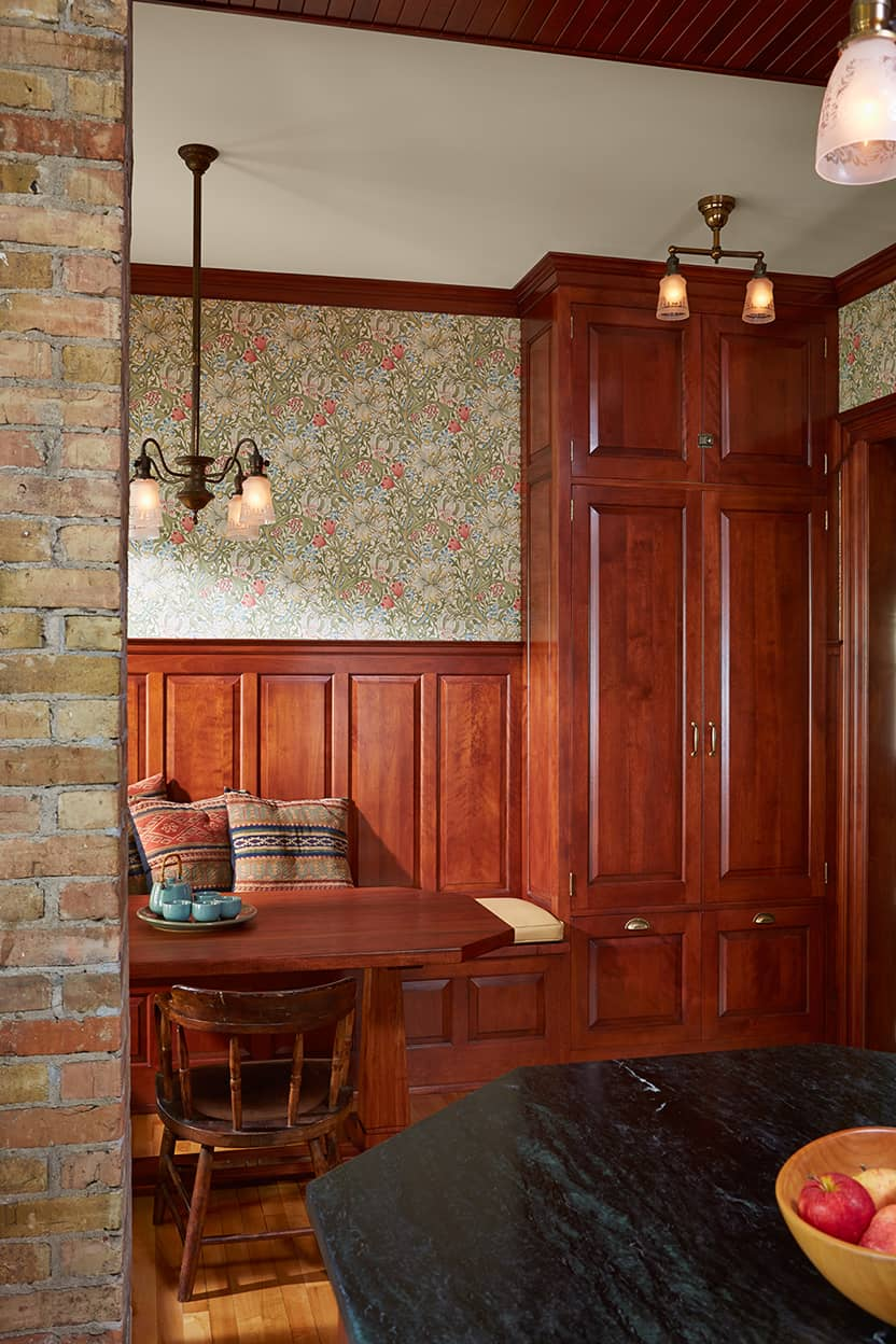 The breakfast room, visually divided from the kitchen by a brick pillar, has bench seating, and shows off the botanical wallpaper in muted greens, ivories, and reds. This picture shows off the kitchen's antiqued brass pendant lighting with glass shades.
