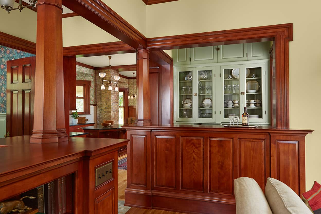 The main cabinet wall of the butler's pantry is sage green, contrasting nicely with the other woodwork, and helping to delineate the different areas of an open space.