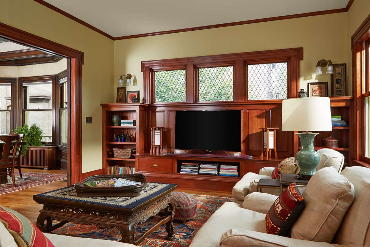 The family room has cream walls, leaded windows over a wall of built-ins, including the entertainment center, and a wall of sash windows, mirroring those you can just glimpse in the dining room.